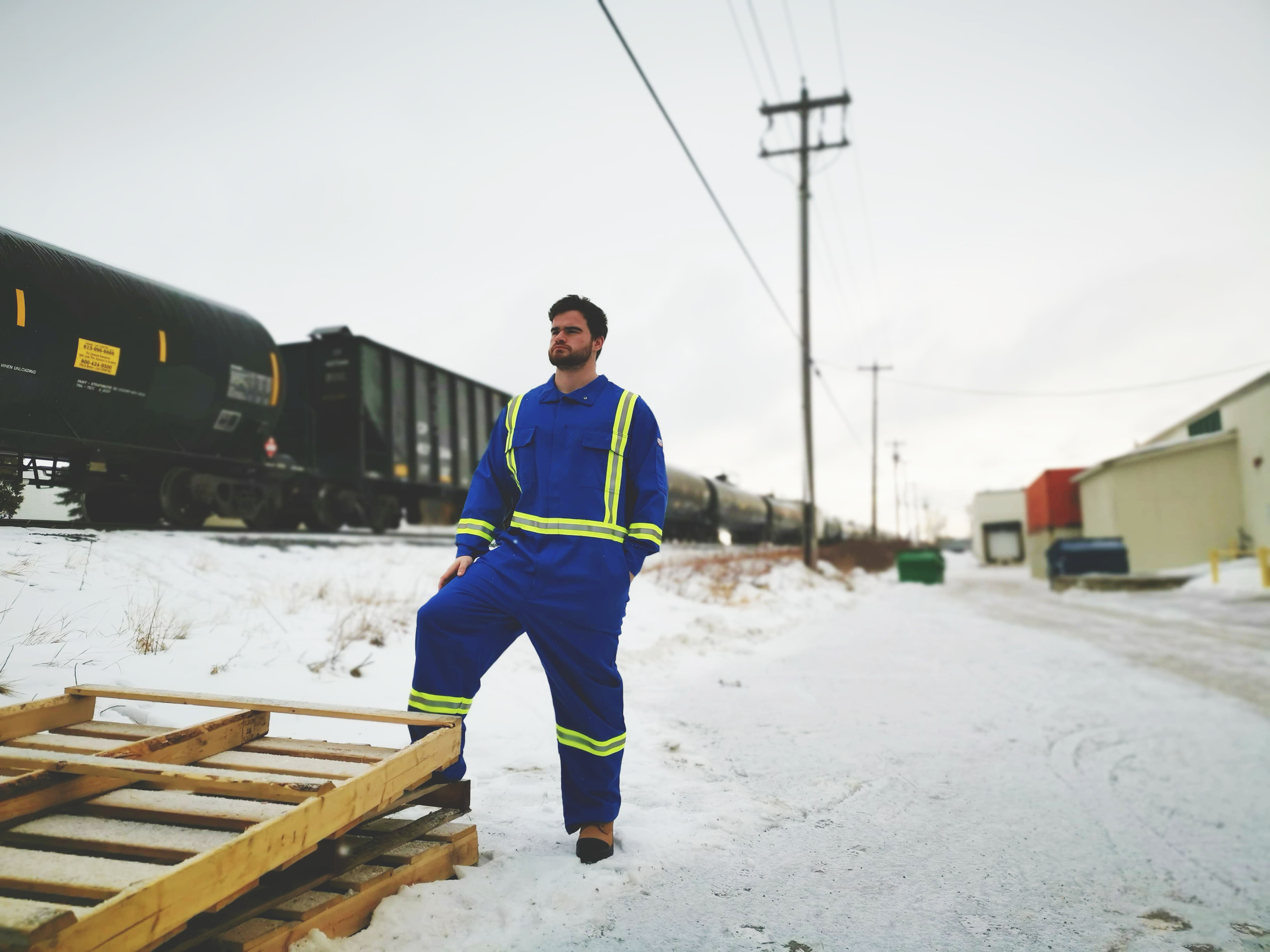 Man in royal blue hi viz striped coveralls stands near a rail yard