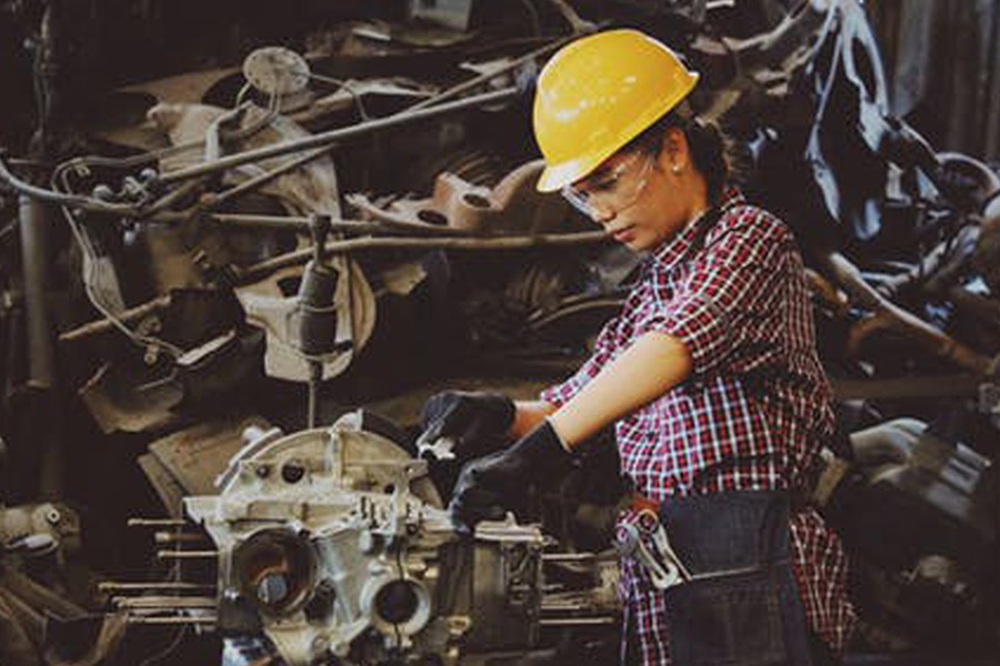 Woman wears eye, head and hand protection while operating machinery
