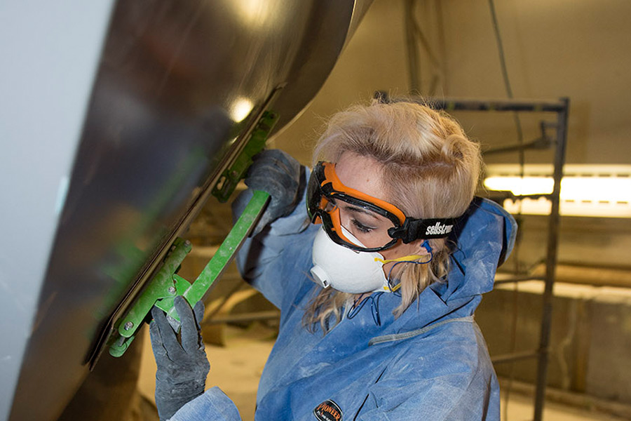 A women in disposable protective workwear works on a car