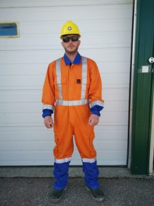 Man wears hi viz FR dual colored coverall and hard hat as personal protective equipment