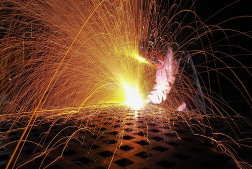 Welding torch creates sparks against metal in the welding process