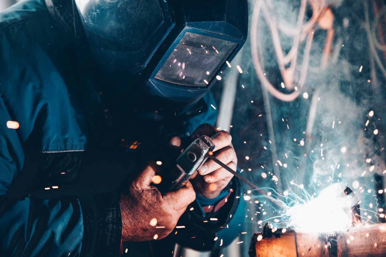 Person in full welding mask uses tools to weld metal together