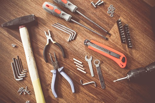 various tools lay on top of a wooden background